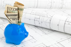 Blue piggybank with dollar bills on home construction plans - home building financing concept